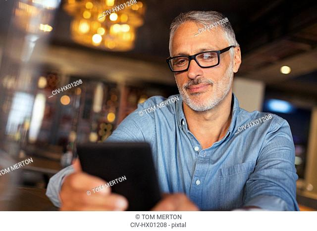 Man texting with cell phone in restaurant