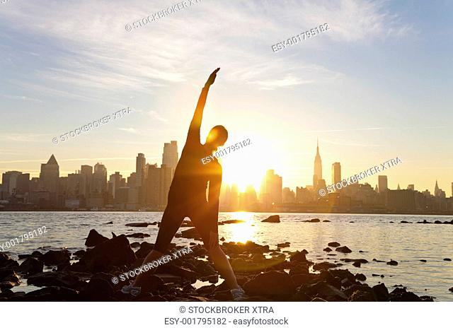 A woman runner stretching in a yoga position in front of the Manhattan skyline, New York City, United States of America, at early morning dawn sunrise