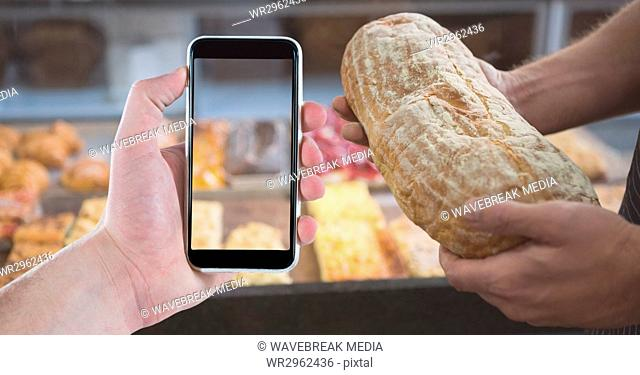 Cropped image of people holding smart phone and bread in coffee shop