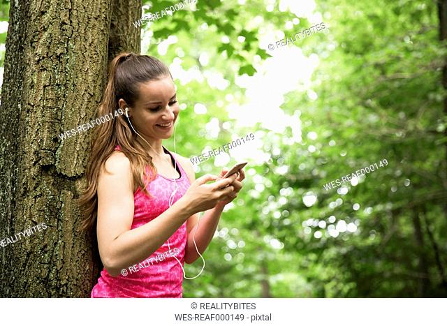 Sportive young woman with smartphone and earbuds