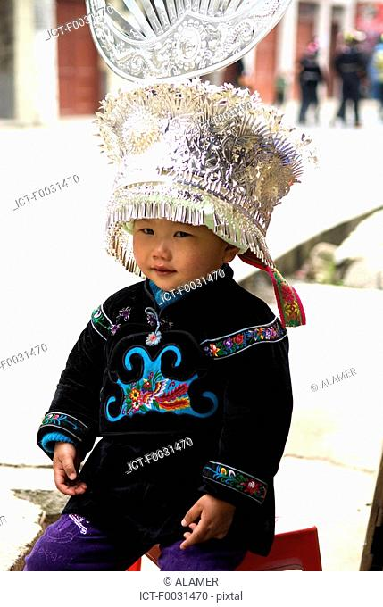 China, Guizhou, Taojiang village, portrait of a child in Miao traditional costume
