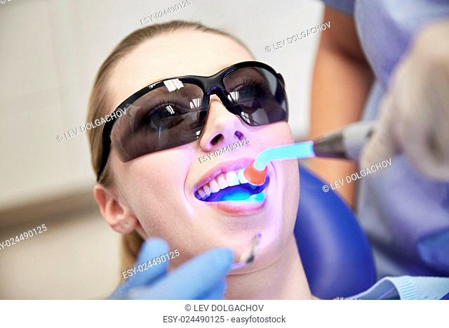 people, medicine, stomatology and health care concept - close up of woman patient in protective eyeglasses or goggles with dental curing light treating teeth at...