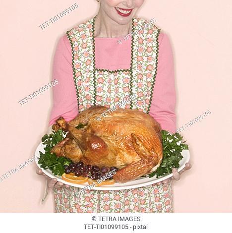 Smiling senior woman holding garnished turkey on plate