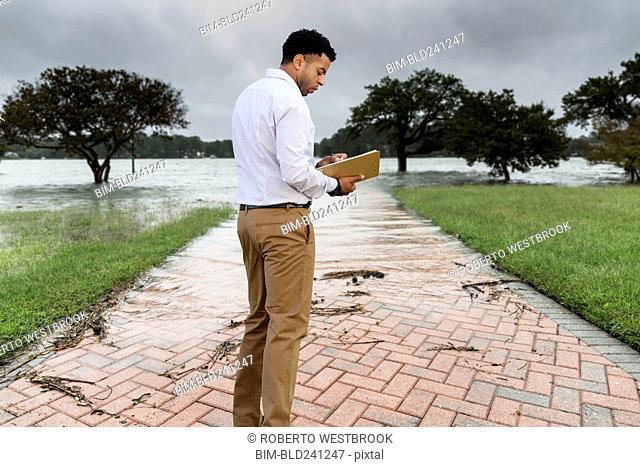 Black insurance adjuster examining flooding damage