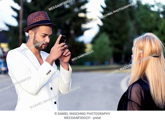 Stylish young man taking a photo of his girlfriend with smartphone