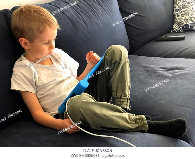 Boy, five years old, lying with a tablet computer in Scania, Sweden