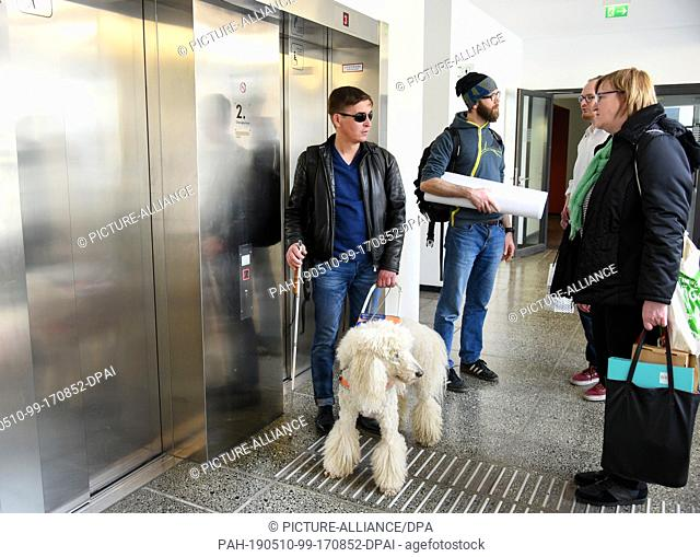 25 April 2019, Saxony, Leipzig: The blind student Sebastian Schulze stands with his guide dog, the king poodle Sunny, in front of the elevators in the seminar...