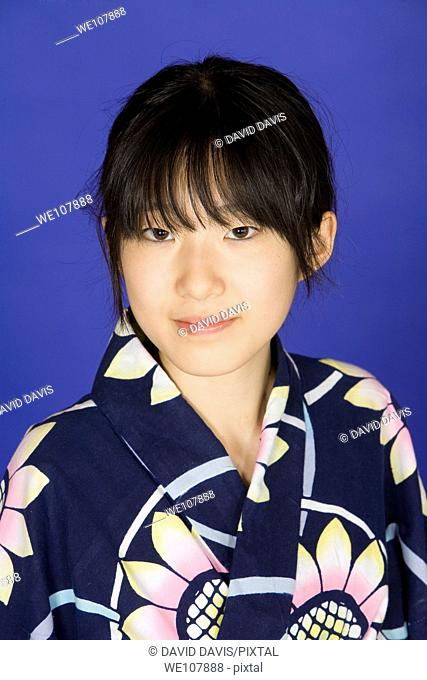Asian teen dressed in a Kimono on a blue background
