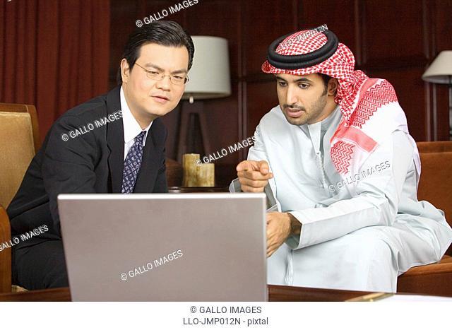 Arab Business Man and Asian Business Man Looking at Laptop Computer Screen  Dubai, United Arab Emirates