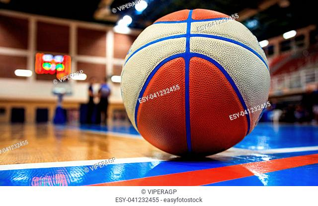 Basketball ball on court floor close up with blurred arena in the background and two defocused coaches talking on court