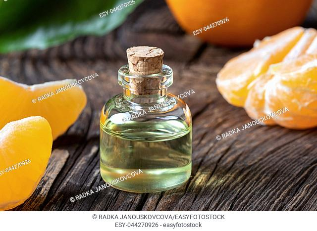 A bottle of essential oil with fresh tangerines on a table