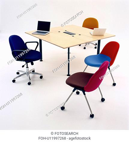 Laptop computer on square table with colourful upholstered office chairs