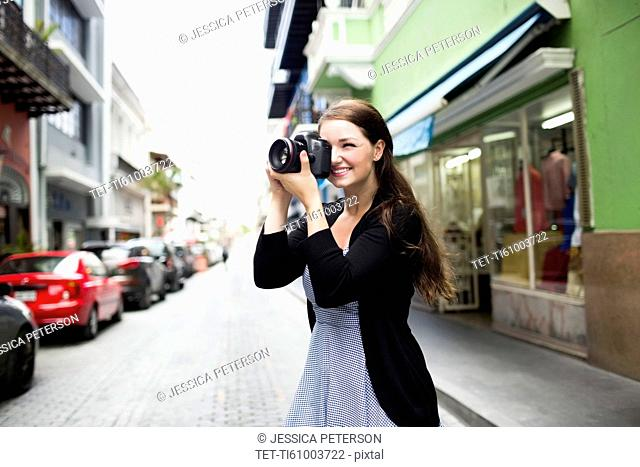 Puerto Rico, San Juan, Woman photographing buildings on street