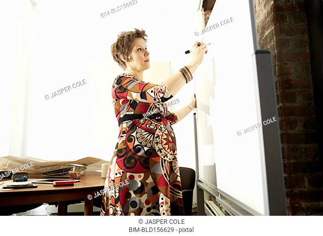 Pregnant businesswoman writing on whiteboard in office