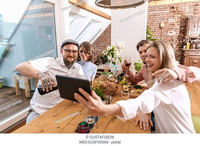 Friends taking selfie with tablet at home