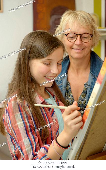 Smiling young teen girl painting with her teacher
