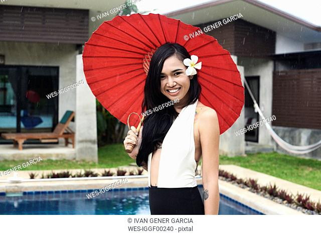 Portrait of smiling woman with flower in her hair holding a red tradtional umbrella at a swimming pool