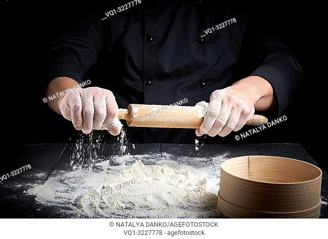 wooden rolling pin in men's hands,white wheat flour scattered on the table