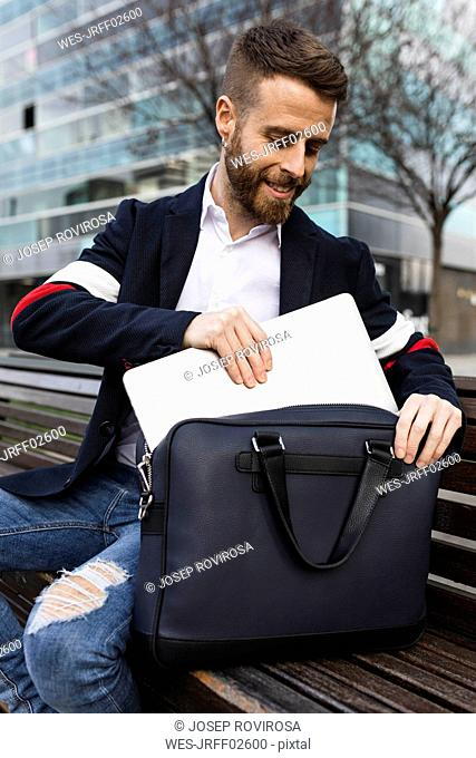 Stylish businessman sitting on bench in the city taking out laptop from bag