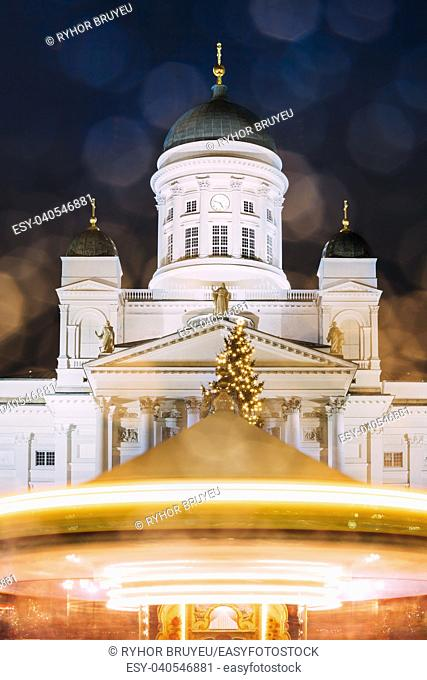 Helsinki, Finland. Xmas Christmas Market On Senate Square With Holiday Carousel And Famous Landmark Is Lutheran Cathedral In Winter Night