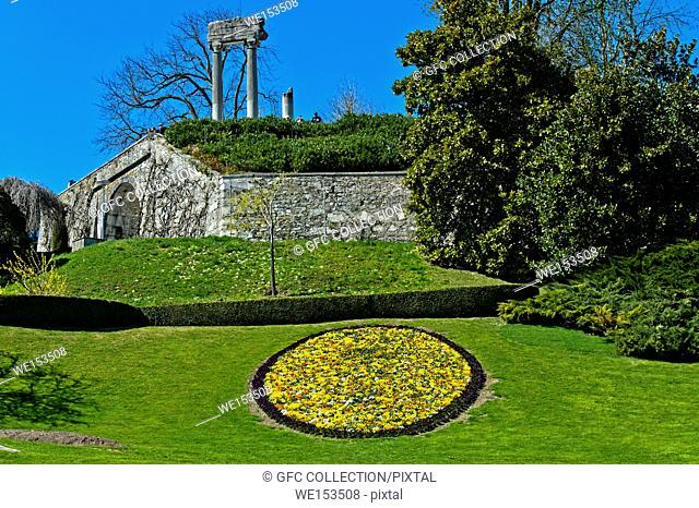 Blumenmedallion im Park, hinten römiische Säulen, Nyon, Waadt, Schweiz / Medallion of spring flowers in the park, roman columns behind, Nyon, Vaud, Switzerland