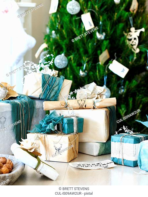 Handmade christmas gift wrapping and christmas crackers in front of christmas tree