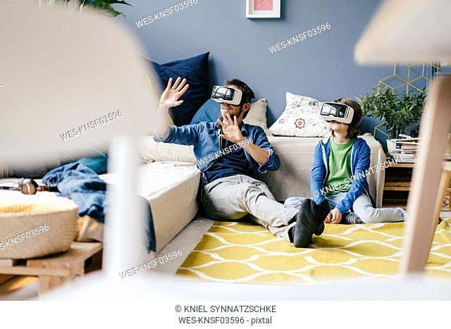 Father and son wearing VR glasses sitting on the floor at home