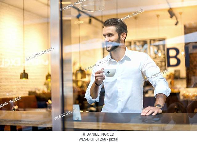 Smiling businessman holding cup of coffee behind windowpane in a cafe
