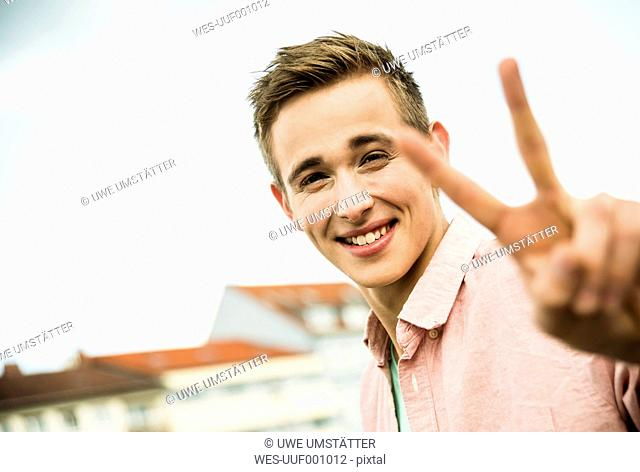Portrait of smiling young man showing Victory sign