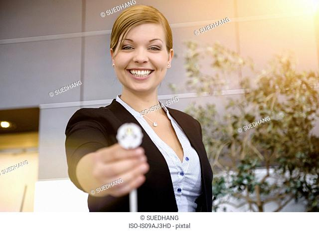 Portrait of young businesswoman holding up cable in office