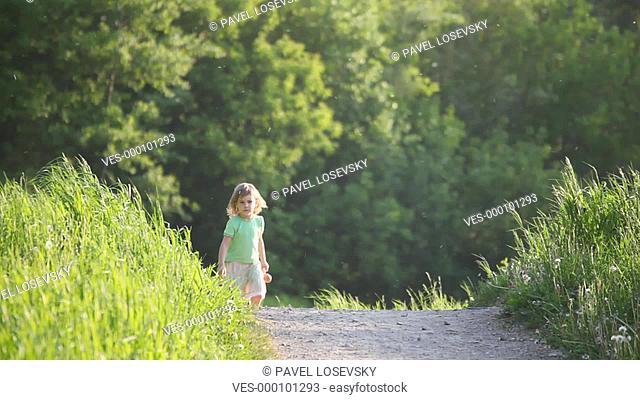 Kleines Mädchen, mit Puppe in der Hand läuft auf einem Feldweg