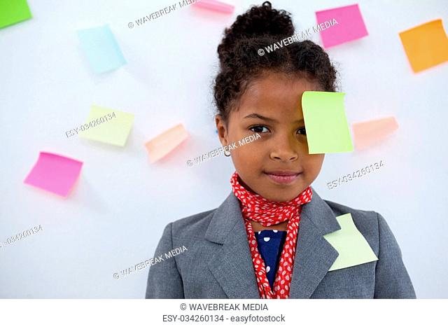 Portrait of businesswoman with sticky notes stuck on head