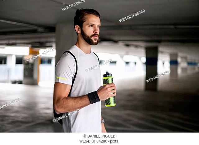 Athlete in parking garage holding drinking bottle
