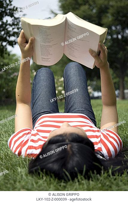 Woman laying in grass, reading book