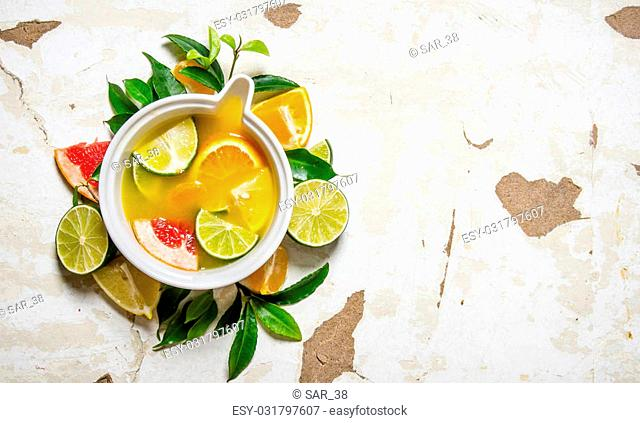 The juice from citrus fruits - grapefruit, orange, tangerine, lemon, lime in a cup with leaves. On rustic background. Free space for text . Top view