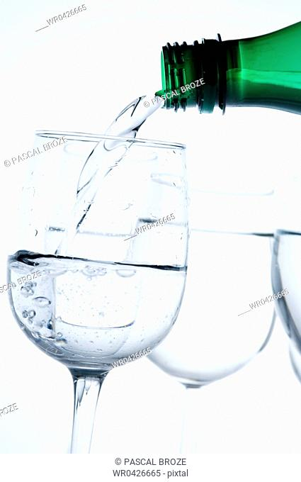 Close-up of water being poured by water bottle into a wine glass