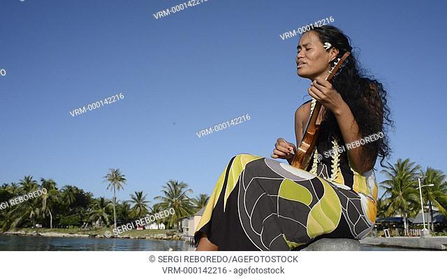 Beautiful local woman playing ukulele in Rangiroa beach, Tuamotu Islands, French Polynesia, South Pacific