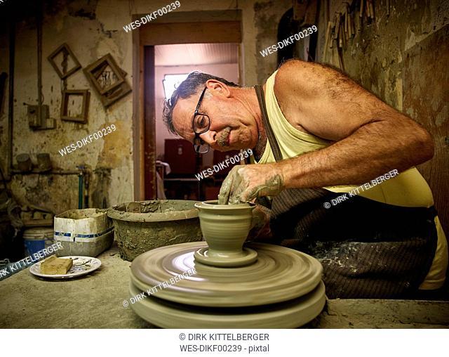Potter in workshop working on vase