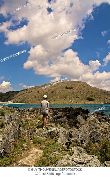 Tourist dreaming in front of the sea and the mountain coast, at Giorgioupolis, Crete, Greece
