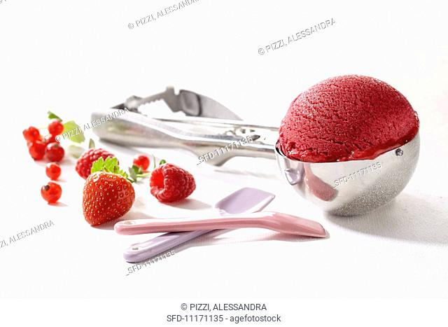 A scoop of raspberry ice cream in an ice cream scoop, with fresh berries and ice cream spoons