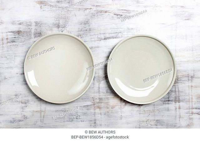 Top view of two empty plates on rustic wooden table