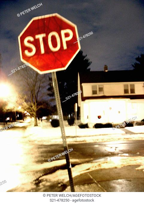 A bright red Stop Sign is captured at night on a surburban street with a slight blur creating a ghostly, painterly effect