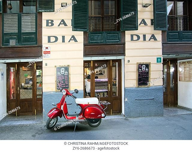Red vespa scooter parked in front of Bar Dia Restaurant on Carrer des Apuntadores in Palma de Mallorca, Balearic islands, Spain