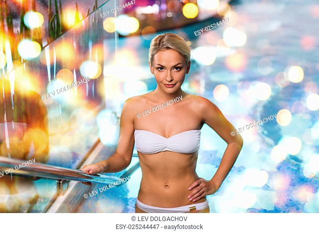 people, beauty, spa, healthy lifestyle and relaxation concept - beautiful young woman in bikini swimsuit raising upstairs in swimming pool over holidays lights