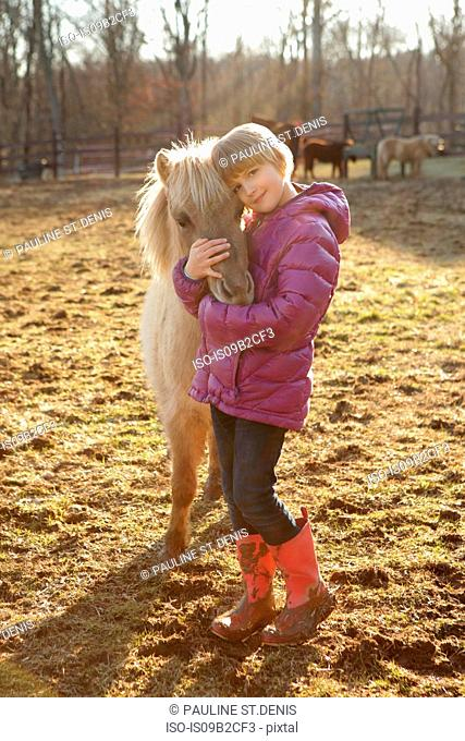 Portrait of young girl outdoors, hugging pony