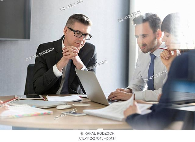 Business people working at laptop in conference room meeting