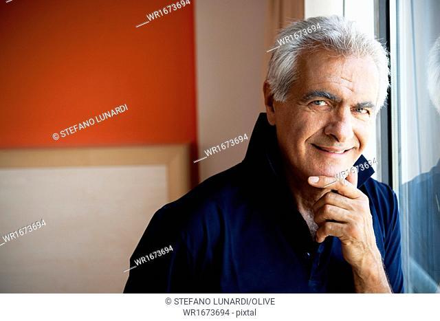Mature man standing at window