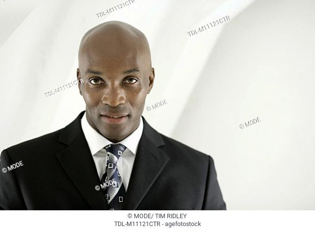 A portrait of a black male in his thirties smartly dressed