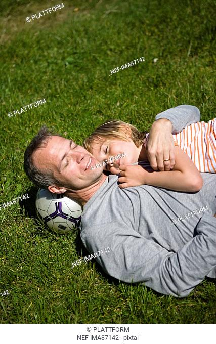 Father with son lying on grass