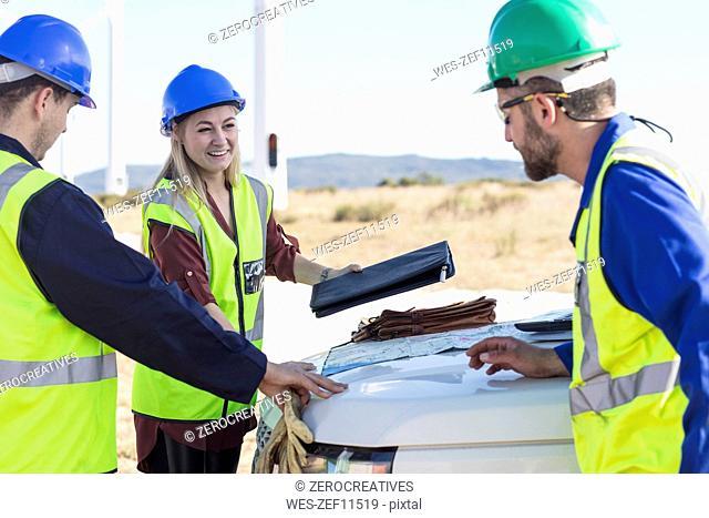 Engineers having a meeting at wind farm